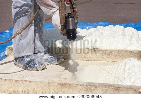 Technician Dressed In A Protective White Uniform Spraying Foam Insulation Using Plural Component Spr