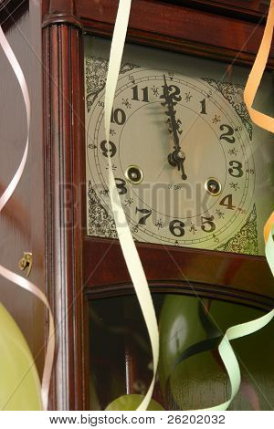 Closeup of wooden wall clock decorated with streamers indicating almost New Year's day time