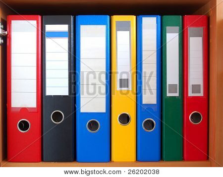 Row of colorful ring binders on shelf