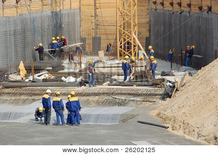 Construction workers working on concrete foundations for large office building