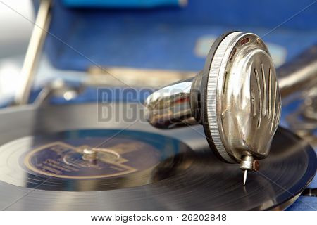 Closeup of old phonograph head over playing record