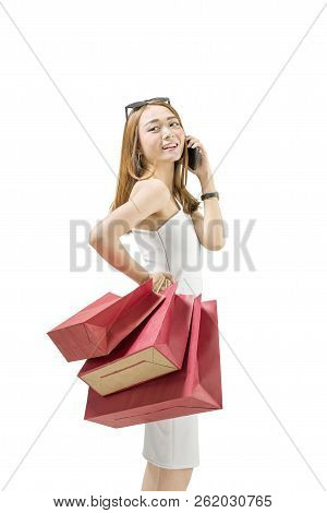 Smiling Asian Girl With Shopping Bags Talking On Mobile Phone Isolated Over White Background