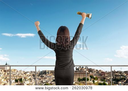 Rear View Of Asian Businesswoman Celebrating Success With Trophy On Office
