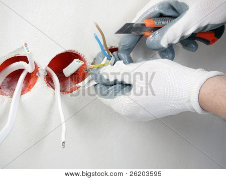 Closeup of electrician's hands stripping electrical wires for wall socket
