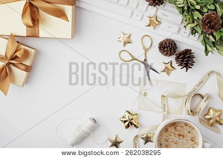 christmas workspace with notebook, christmas gift wrapping tools and ornaments. Flat lay, top view, copy space