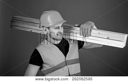 Man In Helmet, Hard Hat And Protective Gloves Holds Wooden Beam, Grey Background. Carpenter, Woodwor