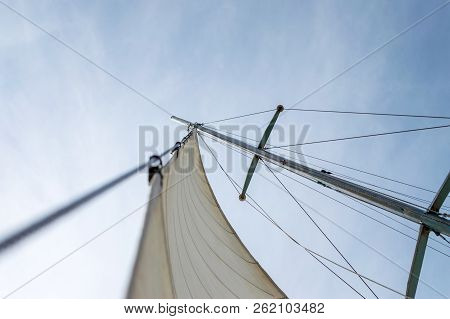 White Sail Of A Sailing Boat Against Sky. Sails Of River Sailing Yacht In The Wind Against The Blue