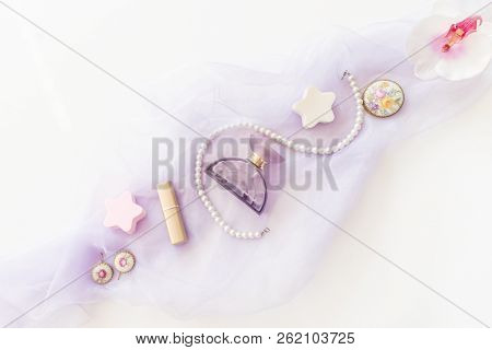Beauty products, decorative cosmetics top view on white background. Flat lay for fashion blogger. Copy space. Lipstick, Lilac scarf, Bottle, bijou, Pearl Beads and Orchid Flower on a White Background poster