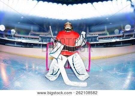 Boy Goaltender Under The Lights Of Hockey Stadium