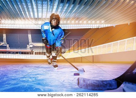 Boy Learning To Pass The Puck At Ice Hockey Rink