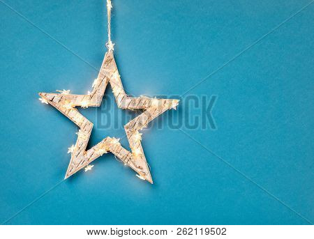Wooden Star Decoration Wrapped In Christmas Lights On A Blue Background