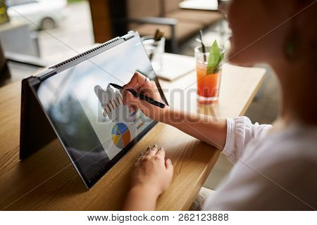 Businesswoman Hand Pointing With Stylus On The Chart Over Convertible Laptop Screen In Tent Mode. Wo