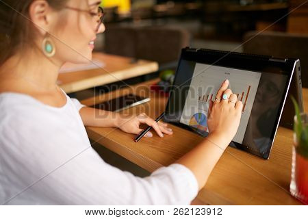 Businesswoman Finger Touching The Chart Over Convertible Laptop Screen In Tent Mode. Freelancer Woma