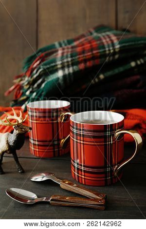 Mugs with hot tea on wood table with rustic background