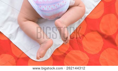 Baby Girl Crawling On Blanket. Bare Legs Of Four-month-old Baby Girl. New Family And Baby Care Conce