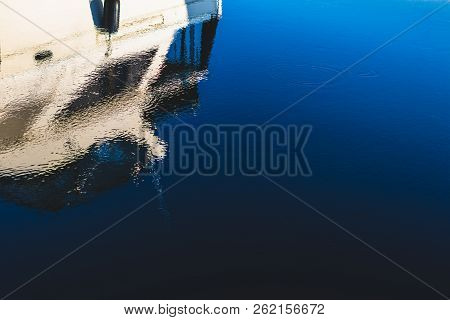Abstract Boat Reflection On A Deep Blue Dark Harbor With Ripples