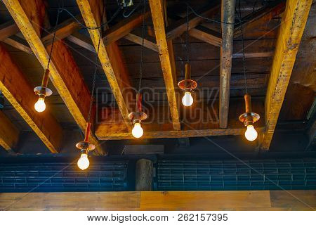 Exposed Two By Eight Floor Board Of Floor Above With Hanging Light Bulbs Lighing The Room
