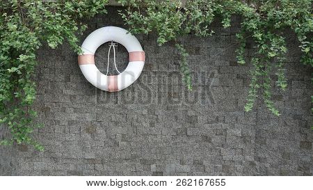 Sos Concept. Rubber Ring Hang On The Wall. Orange Life Saving Rubber. Red Lifebelt On Wall Near The