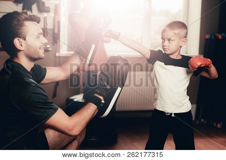 Father And Son Boxing Exercises Training In Gym. Parenthood Relationship. Sporty Family Concept. Act