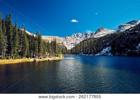 Lake Verna with rocks and mountains around at autumn. Rocky Mountain National Park in Colorado, USA.