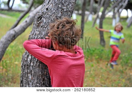 Two Kids Playing Hide And Seek In Park