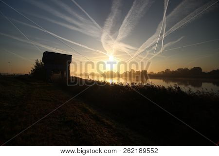 Sunrise With Colored Aircraft Trails, Fog On The Meadows And Dyke At River Hollandsche Ijssel In The