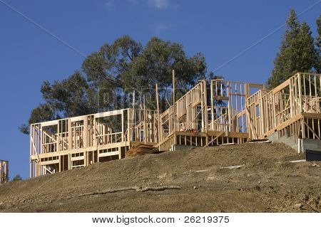 A large modern wood framed house under construction with carpenters completing the roof rafter framing