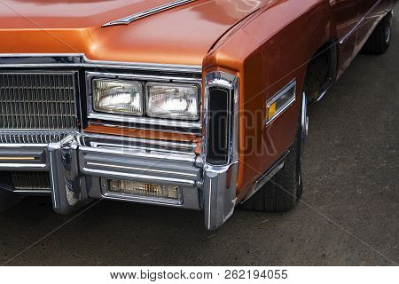 A Closeup Of The Headlights And Front Bumper On A Vintage American Automobile. Polished Shiny Car On