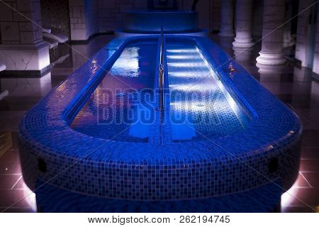 A Luxury Pillared Spa Hall With The Illuminated Plunge Pool In The Centre. An Empty Beautiful Blue-t