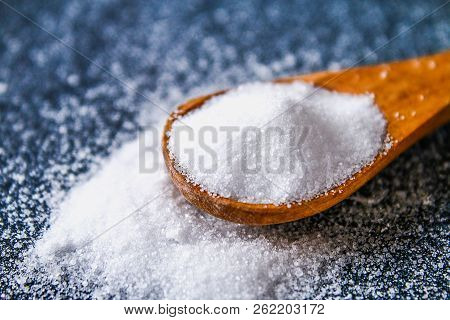 Crystals Of Shallow Salt In A Scoop, Spoon On A Dark Gray Table. Background For Advertising Salt. Ta