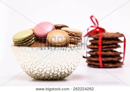 Colored macarons in bowl and chocolate cookies with red ribbon on white background