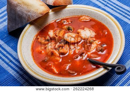 Delisious fisherman stew with bread on plate