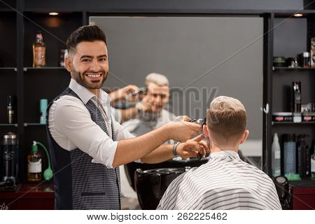 Smiling Hairstylist Working With Client In Barbershop. Bearded Barber Looking At Camera And Trimming