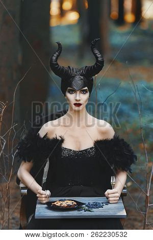 Beautiful And Fashionable Brunette Slim Model Girl In The Image Of Maleficent With Fork And Knife In