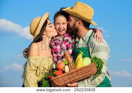 Parents And Daughter Farmers Celebrate Harvest Holiday. Family Farmers Hug Kiss Kid Hold Basket Fall