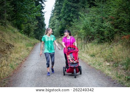 Two women in their 30s walking and talking together on a trail with pushing a baby stroller
