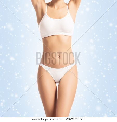Young, sporty, fit and healthy girl over winter background. Sporty female body in white slimming underwear. Christmas concept.