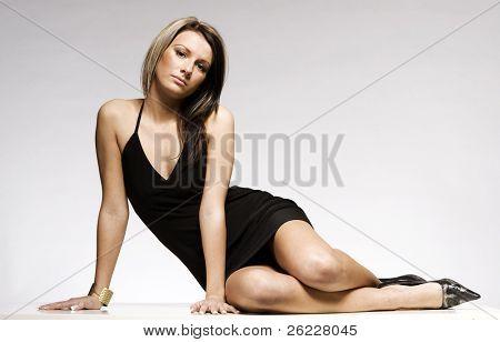 beautiful blonde girl wearing black mini dress posing on grey background