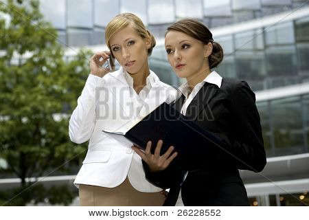 two attractive businesswomen talking on the phone and holding a notebook outdoors