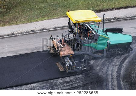 Asphalt Paver Machine Or Paver Finisher Places A Layer Of Fresh Hot Asphalt With Steam. Road Constru