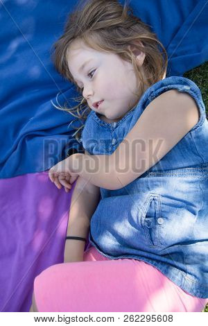 Four Years Old Blonde Girl Lying On Towels In The Green Grass Of Park Looking Sideway With Thoughtfu