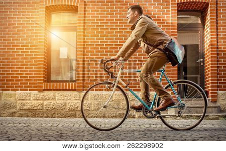 Young stylish businessman go to work on his sport retro bike in sunny day.