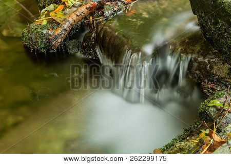 Nature Waterfall At Mountain River Cascade. Colorful Green Mossy Rocks, Waterfall And Cascade. Natur