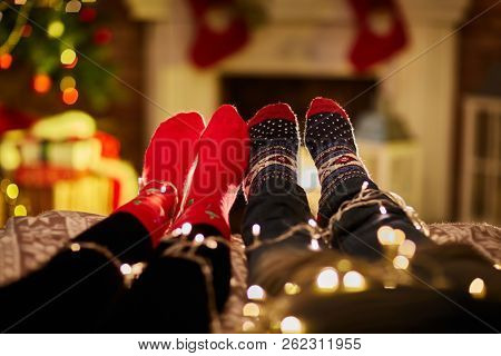 Christmas couple at home in Winter. Feet of a couple at home in Christmas time. Christmas tree and fireplace in background.
