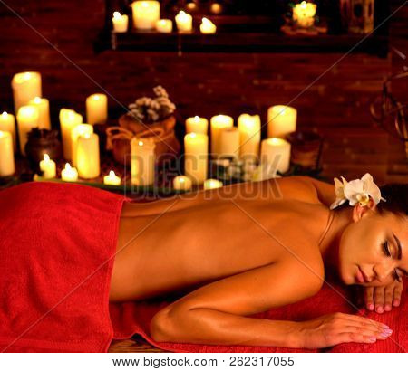 Massage of woman in spa salon. Girl on candles background in massage spa salon. Free massage day in wellness center.