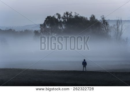 Dramatic Nature Landscape With A Man Standing, Alone In The Cold, On A Meadow, Contemplating The Den