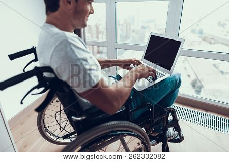 Disabled Man Holding Laptop And Typing On Lap. Closeup Of Handsome Person Wears T-shirt And Blue Jea