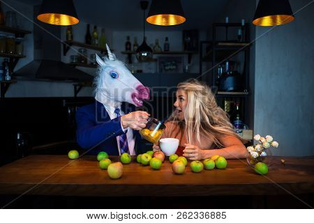 Unusual Couple At The Bar Counter In Stylish Apartments With Food And Drinks. Funny Guy In Comical M