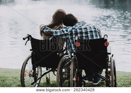 Disabled People On Wheelchairs Near Lake In Park. Disabled Young Man. Woman On Wheelchair. Relaxing