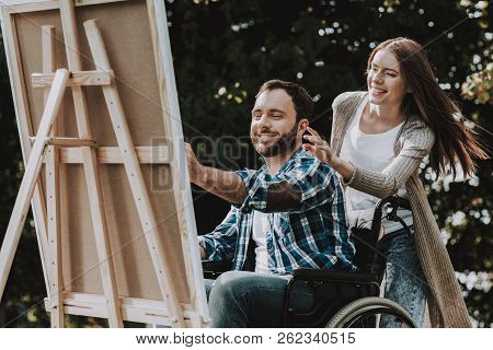 Disabled Young Man On Wheelchairs Drawing In Park. Disabled Young Man. Smiling Woman. Relaxing In Su